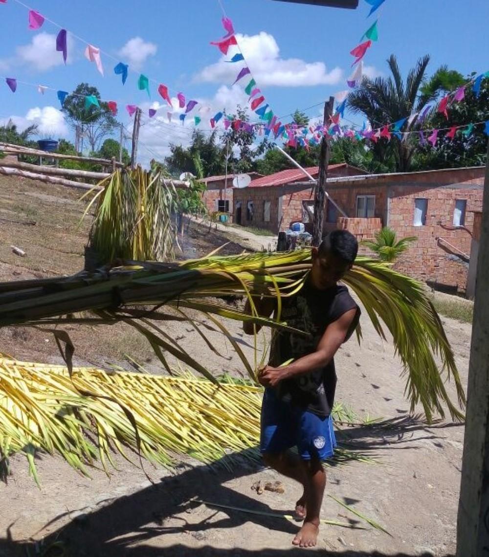 Ajuri da comunidade carregando os feixos de palha para serem aberto no Barracão Uka Nuan [Barracão Grande]