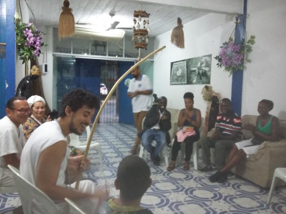 O grupo aprecia os toques de berimbau e os cantos.  Victor, a criança, faz coro.